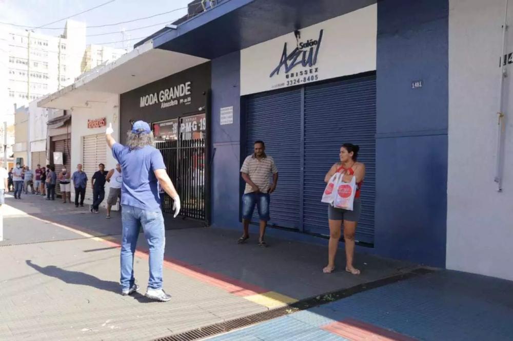 Funcionário organizava fila em frente a lotérica no Centro (Foto: Kisie Aionã)