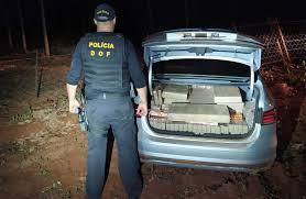 Policial do DOF ao lado do veículo apreendido com a droga. (Foto: DOF)
