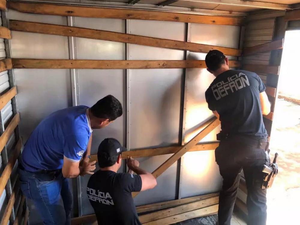 Policiais retiram fundo falso onde estavam fardos de maconha (Foto: Divulgação)