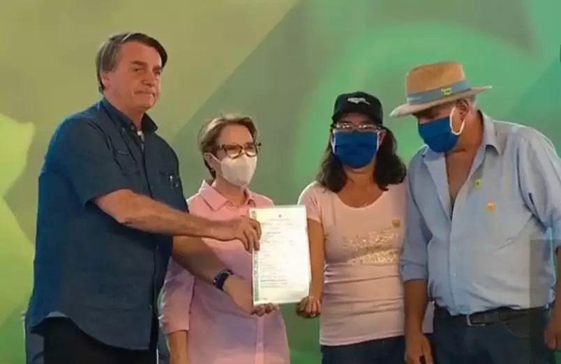 Bolsonaro e Tereza Cristina (à esquerda) entregam título para assentados. (Foto: Reprodução)