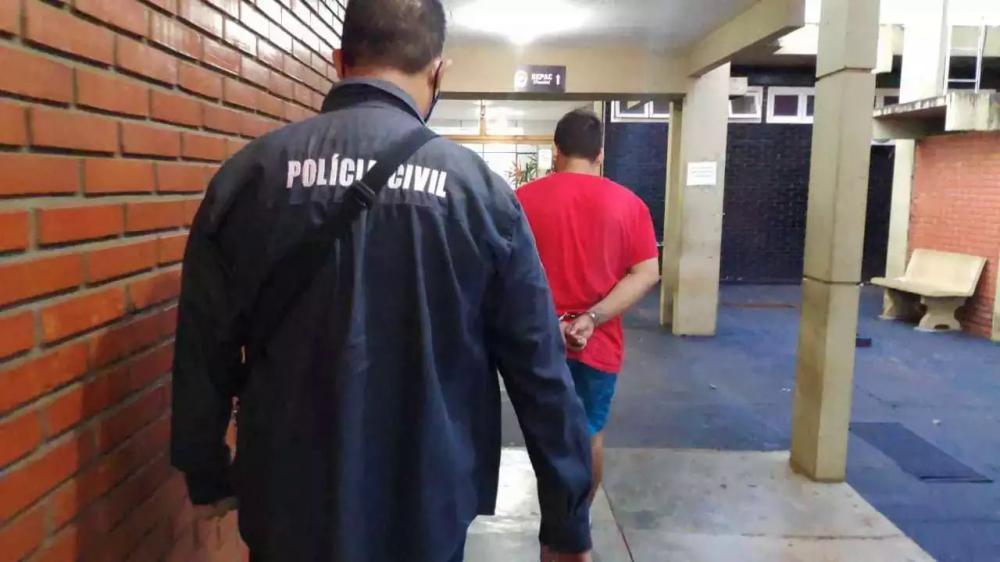 Universitário preso em Dourados é conduzido por policial em delegacia (Foto: Adilson Domingos/Arquivo)